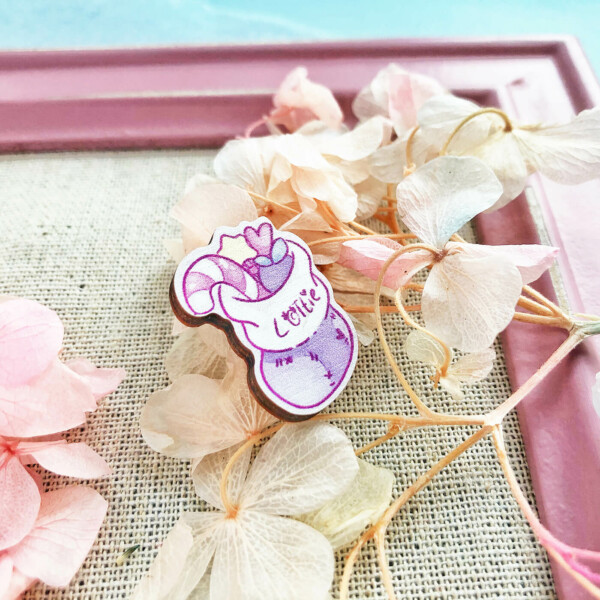 """A cute wooden pin showing an illustration of a Christmas stocking. The stocking is filled with sweets, and the front reads """"Lottie""""."""