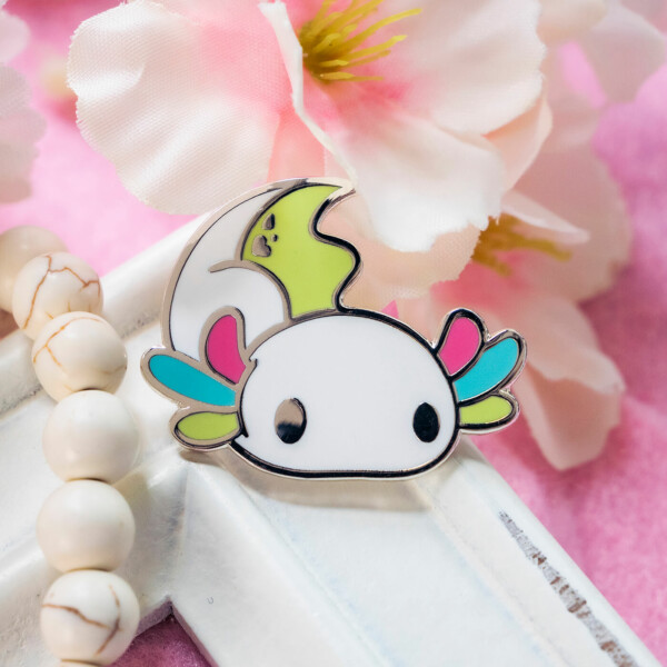 A cute cartoon style axolotl hard enamel pin with raised edges in silver plated metal