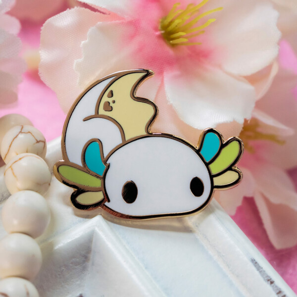 A cute cartoon style axolotl hard enamel pin with raised edges in gold plated metal