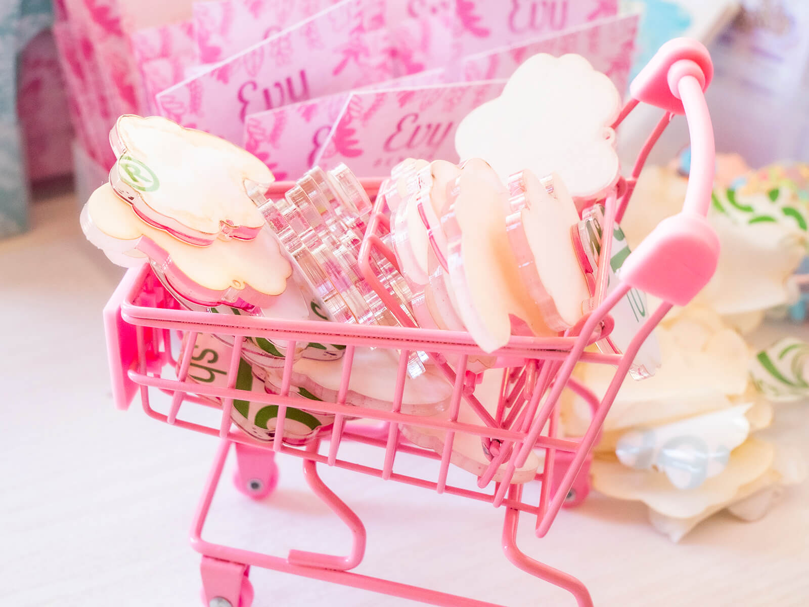 A miniature shopping cart filled with unpeeled charms. Unpeeled charms have a layer of paper or plastic over them, which then has to be peeled in order to reveal the design.