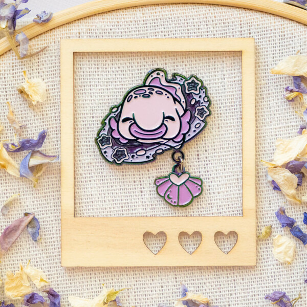 A cosmic blobfish enamel pin with a dangle tail fin. The blob fish is designed in a cute kawaii cartoon style, and the design shows her surrounded by a cluster circle of stars and space.