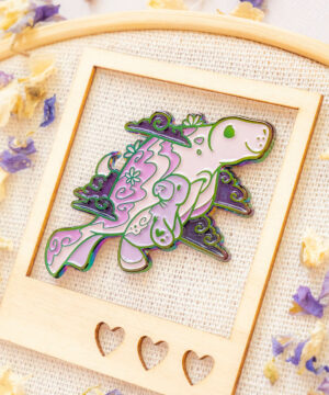 A manatee enamel pin featuring a manatee mum swimming with her pup through cosmic clouds and a crescent moon. Soft enamel and raised metal edges.