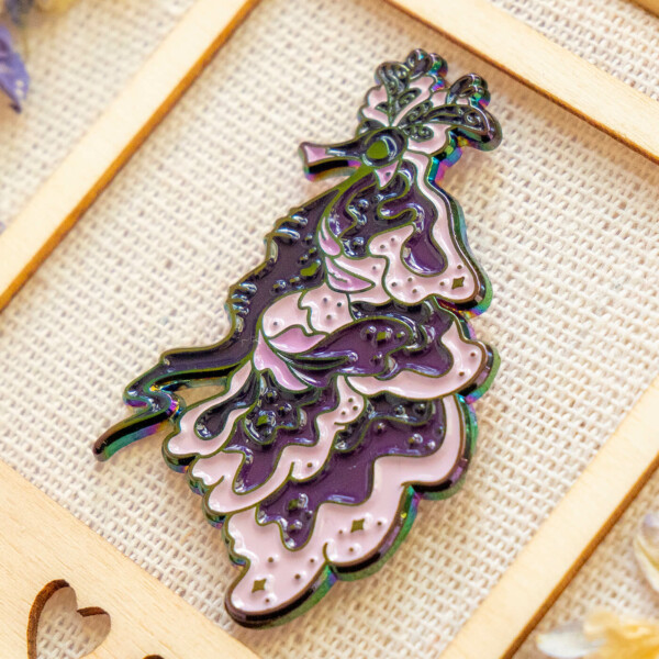 An enamel pin made with subtle rainbow metal plating and soft enamel filling. The pin design features a stylized take on the Australian weedy sea dragon. The sea dragon is decorated with tiny stars and shimmer symbols.